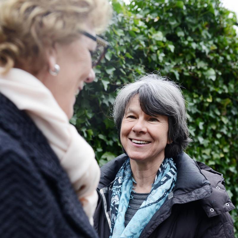 Twee vrouwen lachen naar elkaar