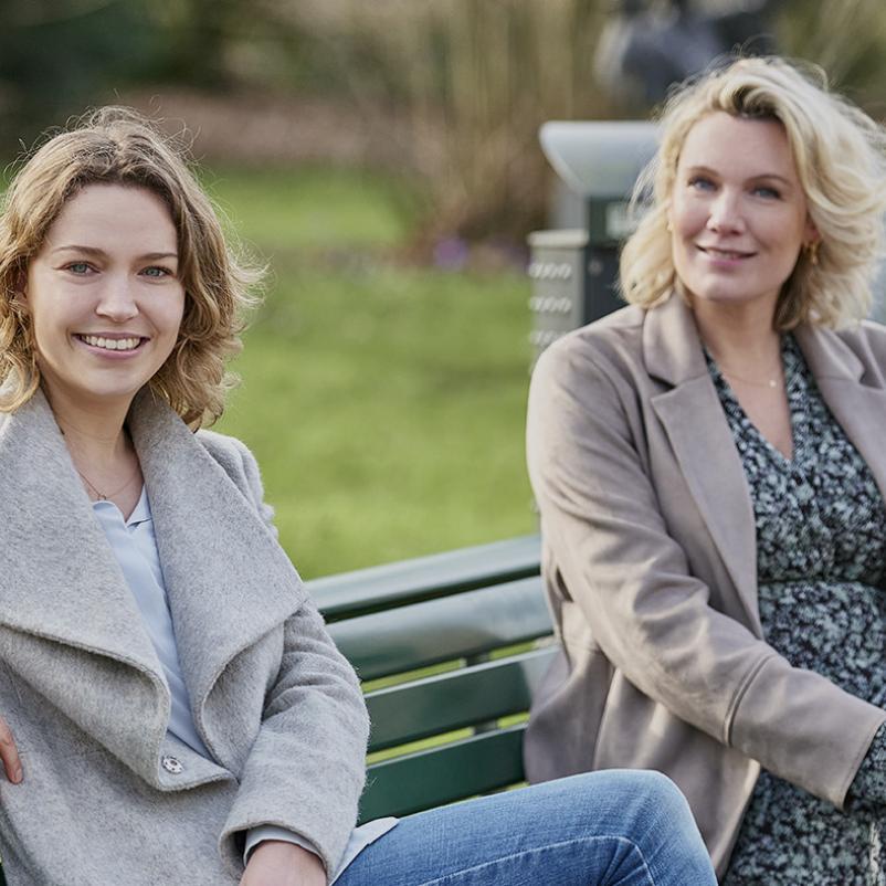 Twee vrouwen zitten op een bankje